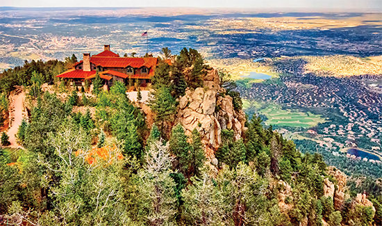 The 8,000 square foot timber lodge and accompanying cabins at Cloud Camp sit atop Cheyenne Mountain, poised to encompass expansive views of eastern Colorado Springs, Pikes Peak and the Rocky Mountains. © Debi Boucher